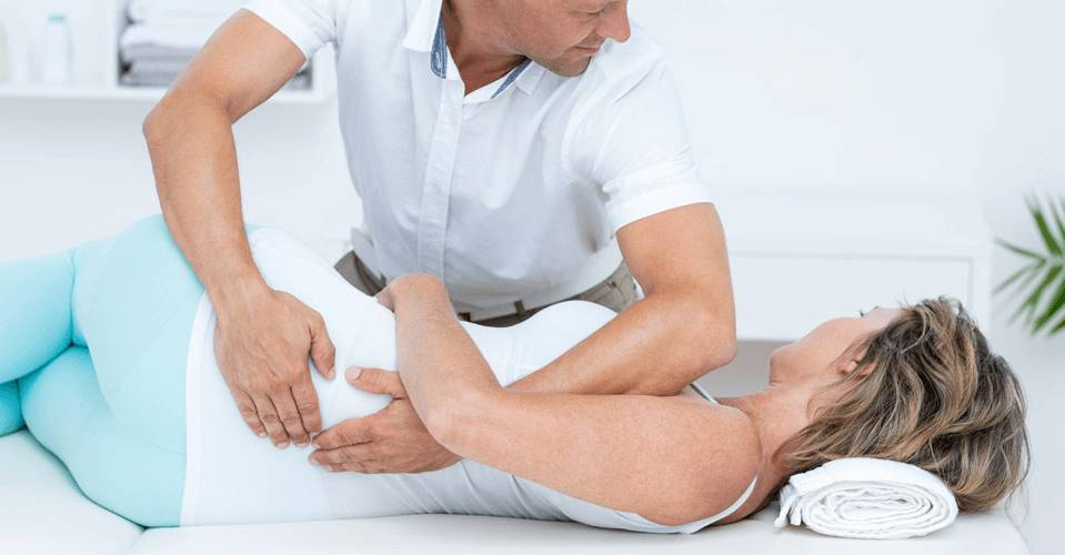 Male Physical therapist treating female patient with lower back pain